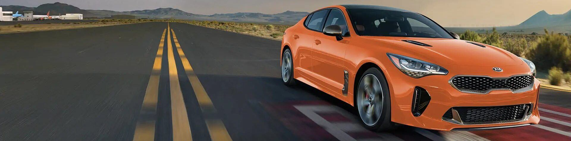 Front side view of a Kia Stinger in orange driving on a country highway